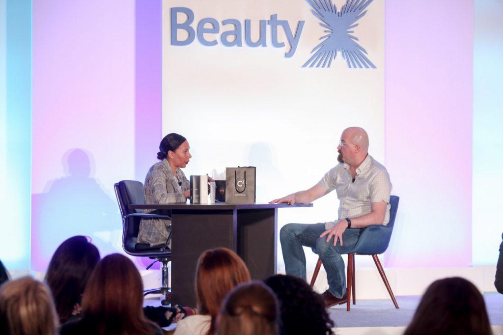 Each brand founder participating in Deskside Domination had five minutes to deliver their pitch to an editor. Here, Adam Fitting of Comprehensive Cranium Care makes his case before Brandie Gilliam, Founder and Creative Director of Thoughtfully Magazine. (BeautyX Media & Influencer Summit)